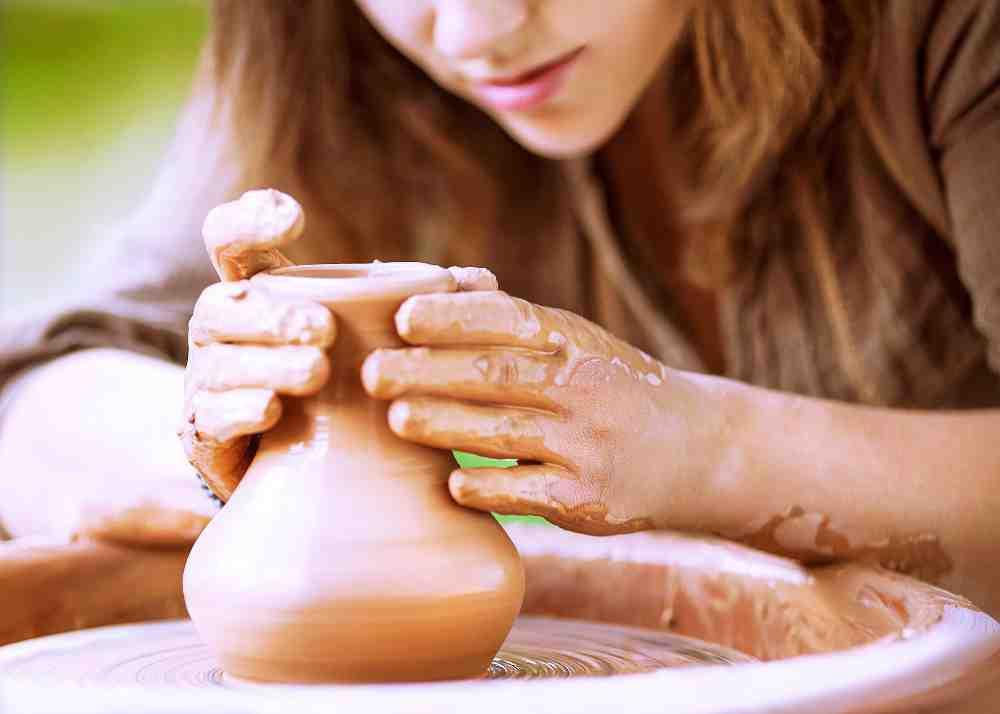 Влияние медитации на креативность и принятие решений. Девушка делает руками глиняный кувшин на гончарном круге.