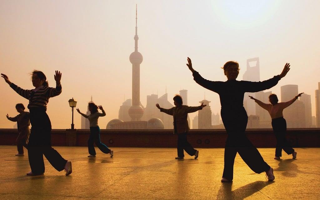 Китайская гимнастика цигун на открытом воздухе в большом городе